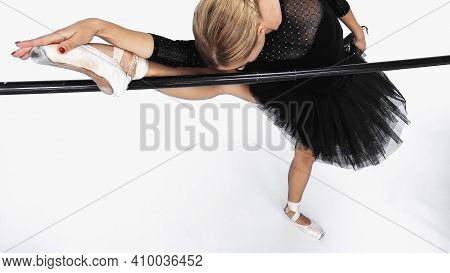 Young Ballerina In Tutu Skirt Stretching Near Barre On White Background