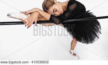 Elegant Ballerina In Tutu Skirt Stretching Near Barre On White Background