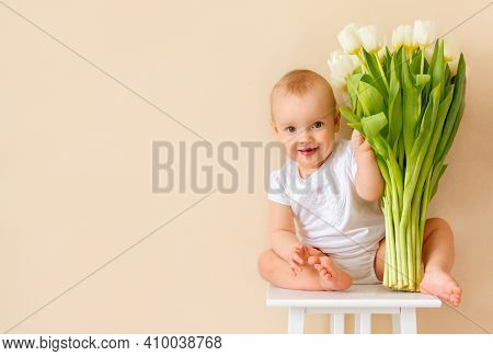 Cute Baby Girl Sit With A Big Bouquet Of Spring White Tulips. A Gift For The Mother\'s Day Holiday,