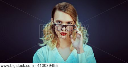 Business style. Studio portrait of a fashionable blonde woman in white blouse and elegant glasses. Optics, eyewear.