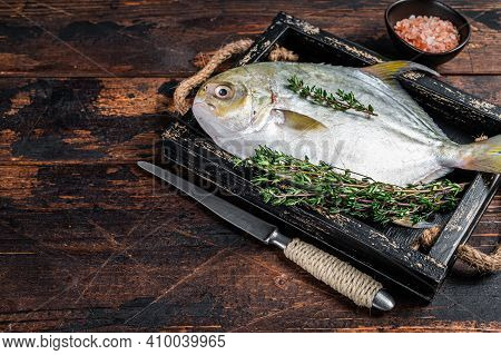 Raw Fish Butterfish Or Pompano With Herbs In A Wooden Tray. Dark Wooden Background. Top View. Copy S