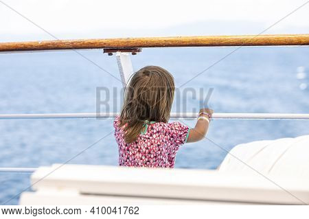 Adorable Young Girl Enjoying Ferry Ride Staring At The Deep Blue Sea. Child Having Fun On Summer Fam