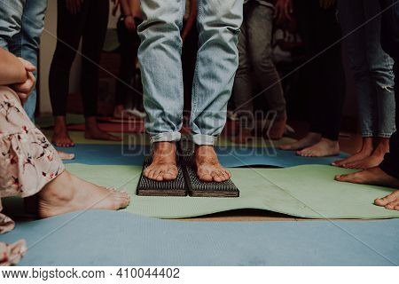 Group practice of standing on nails. Closeup of yoga person standing on sadhu board with sharp nails