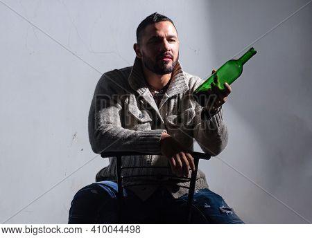 Sad Crying Drunk Man With Bottle Of Alcohol. Hispanic Guy Feeling Lonely And Melancholy