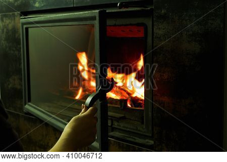 A Woman's Hand Opens The Glass Door Of The Fireplace In Which The Wood Is Burning. Modern Closed Fir