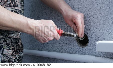 A Man At Home Repairs An Outlet Using Pliers, The Stage Of Work On Installing An Electrical Outlet N
