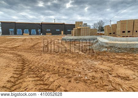 Horizontal Shot Of The Parking Lot Dirt Work Behind A New Restaurant Construction Site.