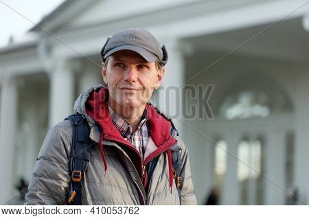 Smiling mature fashionable  Caucasian man in a down coat and fleece hat standing with backpack against a classic style pavilion