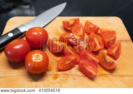 Wooden Cutting Board With A Small Knife And Cherry Tomatoes Cut In Quarters On Top. Cutting Tomatoes