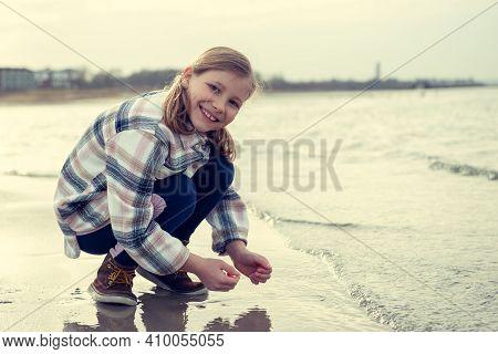 Portrair Of Happy Beautiful Child Girl Playing On Baltic Sea Beach
