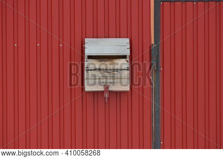 One Gray Wooden Mailbox Hanging On A Red Metal Fence Wall In The Street