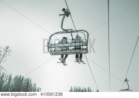 Ski Lift On The Slop In Mountain Ski Resort With Skiers On The Lift. Cableway For Tourists, Skiers A