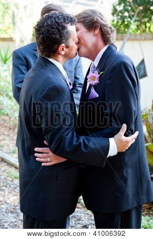 Handsome gay couple kissing at their marriage ceremony.