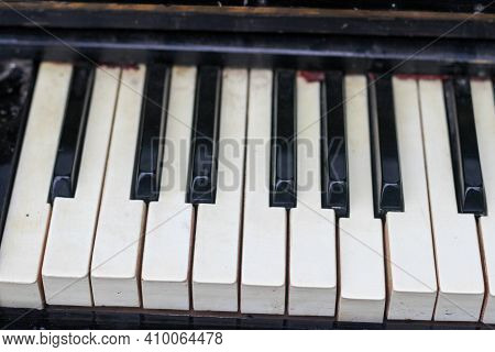 The Keyboard Of A Very Old Abandoned Piano Is Covered With Dust, Some Keys Have Dropped, Some Are Ab