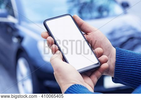 Man Holds A Smartphone In His Hands. Mock Up Phone With White Screen On The Background Of The Car.