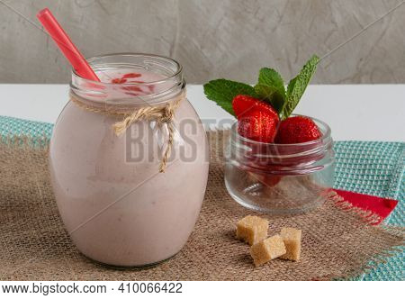 Delicious And Healthy Strawberry Milkshake In A Jar, Strawberries And Cane Sugar With A Red Heart Of