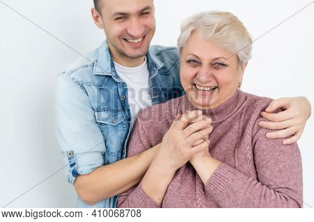 Family, Generation And People Concept - Happy Smiling Senior Mother With Adult Son Hugging At Home