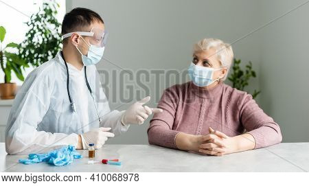In Modern Private Clinic Doctor Is Listening Heart Of Senior Patient Sitting On Hospital Bed. Health