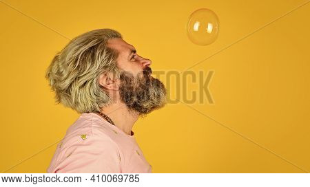 Infantility Concept. Happy Playful Bearded Hipster And Soap Bubbles. Happiness And Joy. Good Vibes.