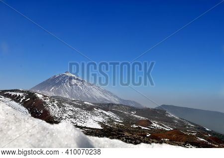 The Snow Reaches The Teide That Is Adorned With A White Mantle Among The Vegetation
