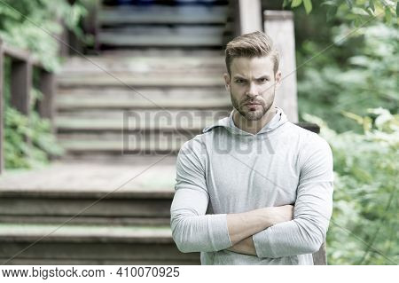 Muscular And Confident. Muscular Man On Summer Day. Athletic Guy Keeping Muscular Arms Crossed At Pa