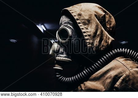 Stalker Warrior In Protective Soviet Gas Mask Profile View Standing On Dark Tunnels Background.