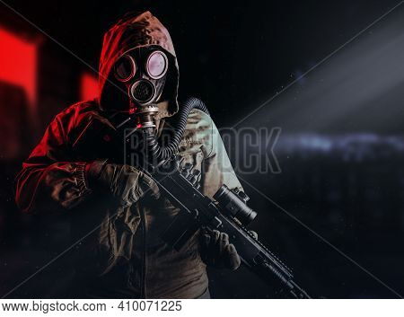 Photo Of A Post Apocalyptic Stalker Soldier In Gas Mask And Hood Jacket Holding Rifle And Standing O