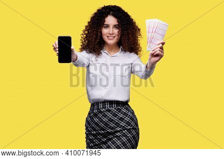 Smiling Woman Holding Mobile Phone And Lottery Tickets. Concept For Online Casino, Lottery, Sports B
