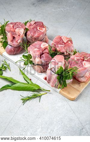 Pork Osso Buco, Shin Pork Shanks With Fresh Aromatic Herbs On White Marmol Board