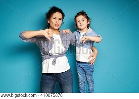 Beautiful Mom And Daughter Equally Dressed Showing Thumbs Down And Expressing Dissatisfaction And Di