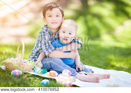 Mixed Race Chinese and Caucasian Boys Outside in Park Playing with Easter Eggs.