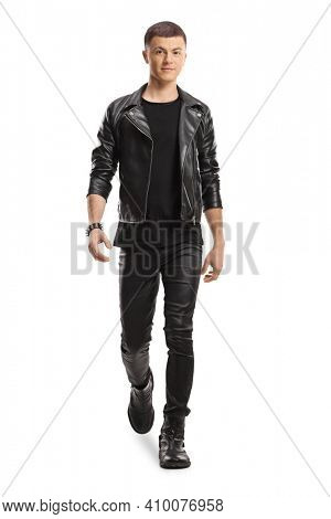 Full length portrait of a guy in leather jacket and pants walking towards camera isolated on white background