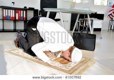 Muslim businessman praying at office