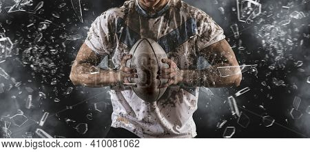 Man rugby player holds ball on dark background. Sports banner. Horizontal copy space background