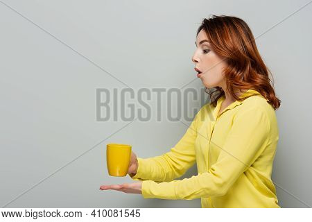Shocked Woman In Yellow Blouse Holding Cup Of Hot Beverage On Grey.