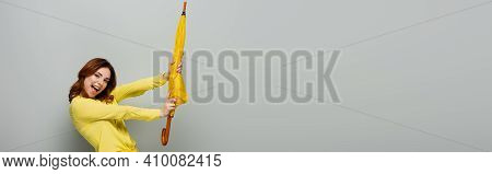 Thrilled Woman Looking At Camera While Standing With Yellow Umbrella On Grey, Banner.