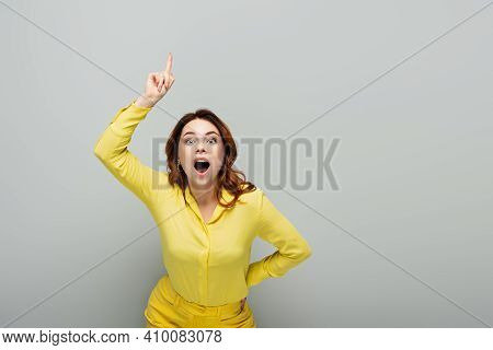 Thrilled Woman Pointing Up With Finger While Standing With Hand On Hip On Grey.