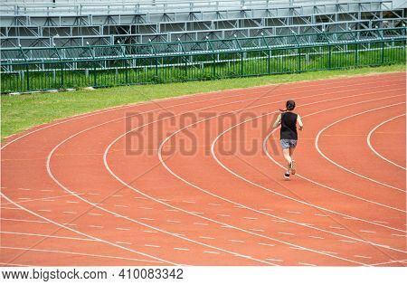 Back View Of Young Athlete Runner Woman Running In The Running Track In Stadium. Running Track Is A