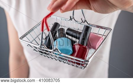 Woman Is Holding A Miniature Shopping Basket With Colorful Bottles Of Nail Polish. Closeup. Concept