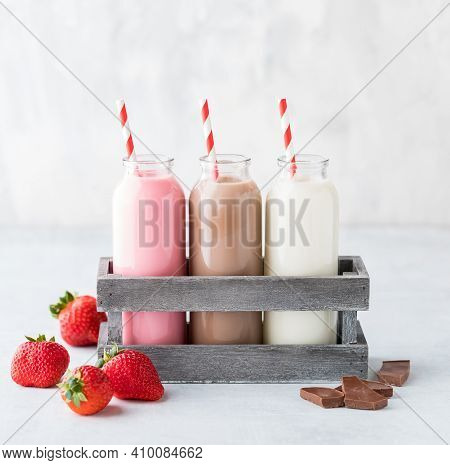 Three Bottles Of Filled With Strawberry, Chocolate And Vanilla Milk With Strawberries And Chocolate