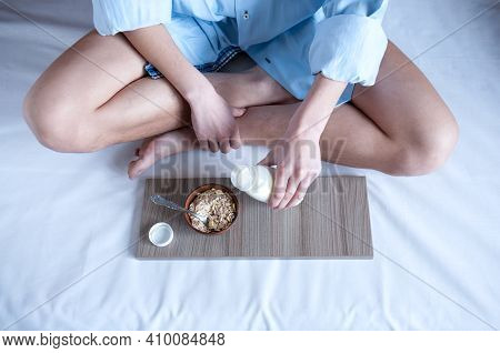 Breakfast In Bed, A Girl In A Blue Shirt Sitting On A White Sheet And Breakfast Cereal With Milk. Th