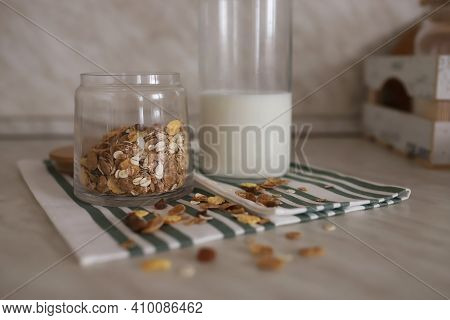 Muesli In A Transparent Jar Stands Next To A Bottle Of Milk On A Table On A Kunjon Table. A Bottle O