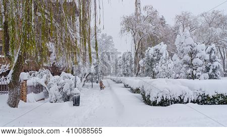 Streets And Buildings Covered In Snow By Day Due To Snowstorm Filomena Falling In Madrid Spain. Peop