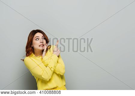 Scared Woman In Yellow Blouse Looking Away And Pointing With Finger On Grey.