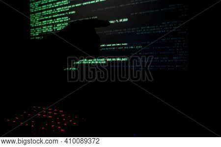 Hacker Pointing To Code On A Computer Monitor In A Dark Room.