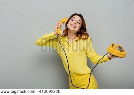 Cheerful Woman In Yellow Blouse Talking On Retro Phone While Standing On Grey.