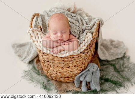 Adorable sweet newborn baby boy sleeping on knitted blanket in the wicker basket. Infant child put his head in hands
