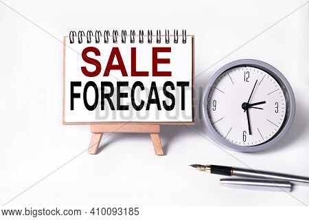 Sale Forecast. Text On White Notepad Paper On White Background. Near The Table Clock
