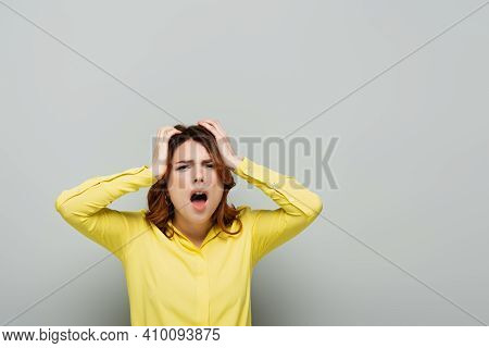 Stressed Woman In Yellow Blouse Screaming While Touching Head On Grey.