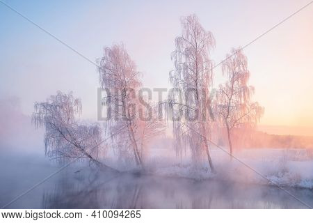 Winter Landscape With Morning Sunlight. Trees Covered With Frost On Riverbank Illuminated With Sunsh